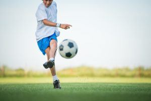 A child playing soccer after a knee injury